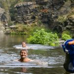 Enduro riders swimming in beautiful natural lagoon