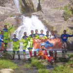 Group of enduro riders near natural waterfall in costa verde tour